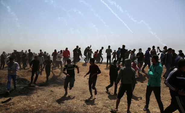 Palestiinalaiset juoksevat kyynelkaasupanoksia suojaan Israelin ja Gazan rajalla perjantaina.