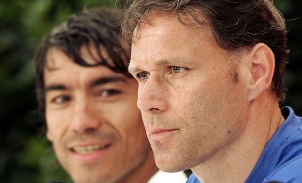 Giovanni van Bronckhorst katselee, kun lehdistön tenttaama valmentaja Marco Van Basten (oik.) vastailee kysymyksiin.