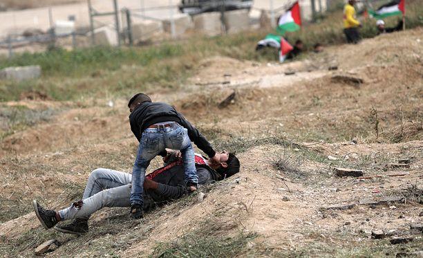 Palestiinalainen mielenosoittaja yritti auttaa Israelin joukkojen haavoittamaa nuorta maaliskuun 30. päivänä Israelin ja Gazan rajalla.