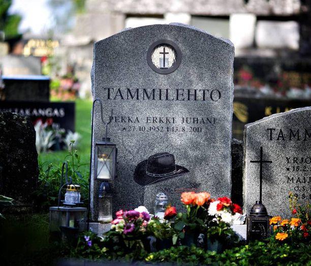 Topin haudalle on tuotu enkeleitä ja kynttilöitä. Hautakiveen on ikuistettu hänen tavaramerkkinsä stetson.