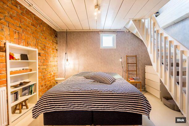 Alakerrassa on viihtyisä paikka sängylle. Huomaa myös rustiikkinen tiiliseinä.