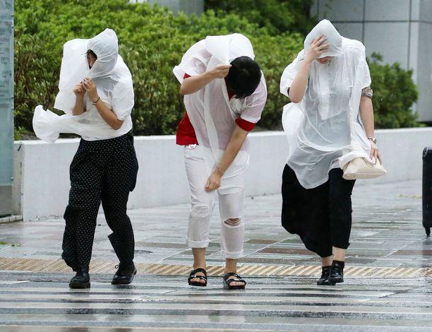 Jalankulkijat taistelevat sateenvarjojensa kanssa.