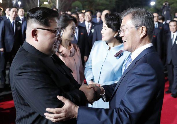 Pohjois- ja Etelä-Korean johtajat tervehtivät toisiaan lämpimästi. Taustalla vaimot.