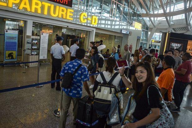 Turistit jonottivat keskiviikkona Denpasarin kansainvälisellä lentokentällä Balilla.