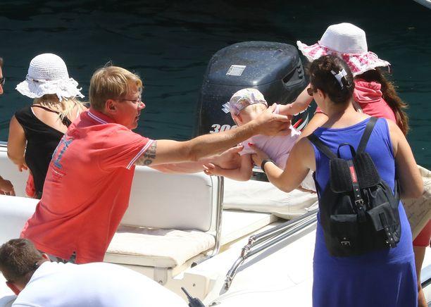 Mika nostaa kaksosiaan veneeseen.