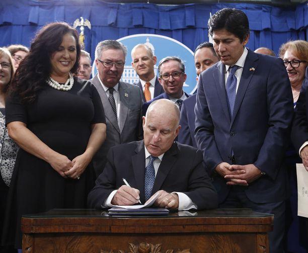 Kuvernööri Jerry Brown allekirjoitti nimellä SB100 tunnetun lain maanantaina. Hänen rinnallaan olivat paikallispoliitikot Lorena Gonzalez Fletcher ja Kevin de Leon.