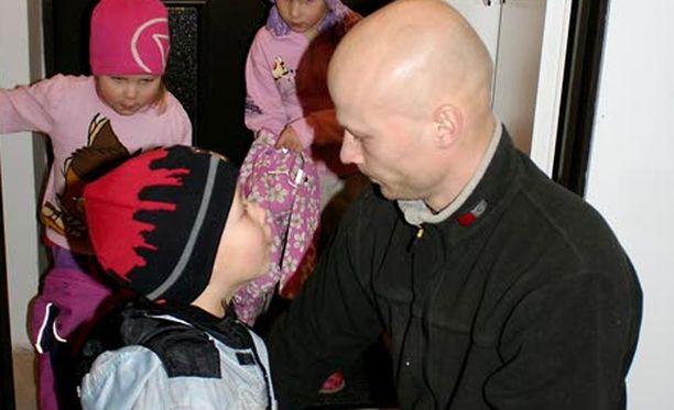 Tero Holm pukee viisivuotiaalle tyttärelleen ja nelivuotiaille kaksosilleen ulkovaatteet päälle, kun ulkona on vielä pimeää. Lapset menevät päiväkotiin jo aamuseitsemältä.