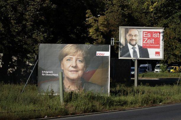 """Merkel ja Schulz kampanjoivat kadunvarsilla rinta rinnan. CDU:n vaalilause kuuluu """"Menestyksekäs Saksalle"""" ja SPD:n """"Nyt on aika""""."""