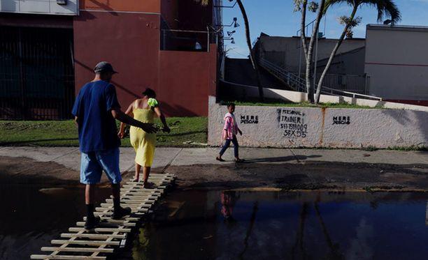 Ihmiset ylittävät tulvaveden peittämää katua pääkaupunki San Juanissa. Puerto Rico on Yhdysvaltain itsehallintoalue, jossa asuu yli kolme miljoonaa ihmistä. Hurrikaani Maria iski saarelle 20.9.