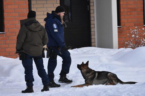 Koira etsi poliisimiesten kanssa jotain kerrostalon pihasta.
