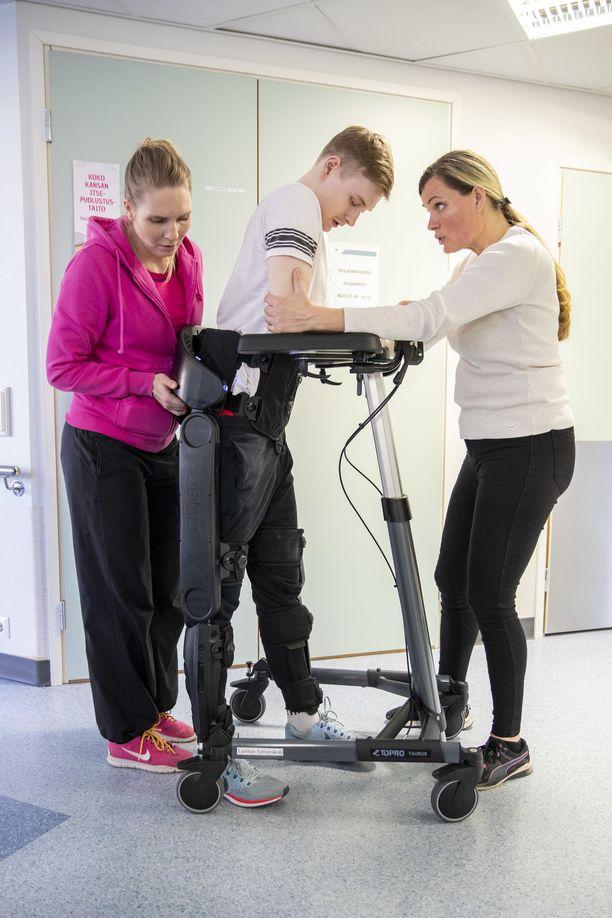 Teemu Tenhunen harjoittelee kävelyä Indego-robotin avulla. Kuvassa oikealla Laitilan terveyskodin kuntoutuspäällikkö Paulina Iiskala.