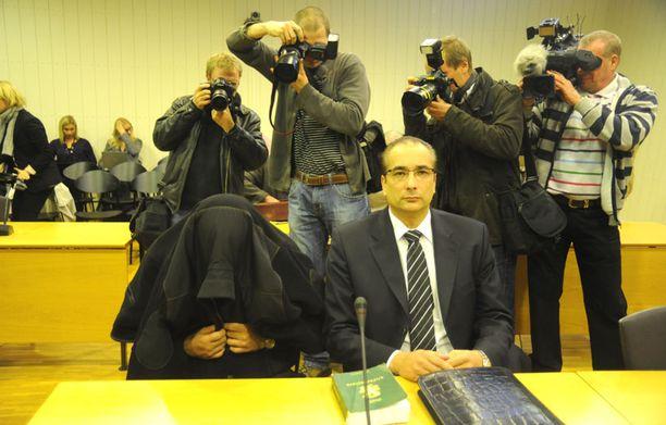 Kolmoissurmista syytetty Esa Åkerlund piiloutui kuvaajilta takkinsa alle. Åkerlundia avustaa oikeudessa asianajaja Heikki Lampela.