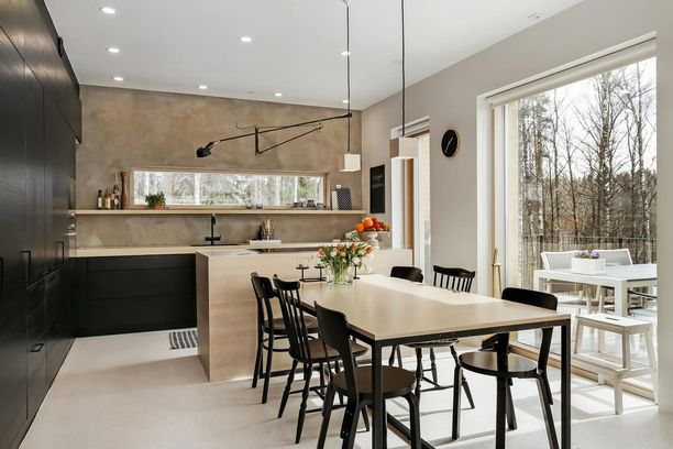 Tämä musta keittiö kuin sulautuu luontoon. Vaalea pöytä, puinen saareke ja saman sävyinen seinä sopivat väriin loistavasti sekä tuovat luonnonläheistä tunnelmaa tilaan yhdessä suuren ikkunan kanssa.