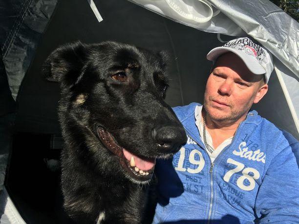 Sakari Sippala ja Sisu-koira yöpyvät teltassa kunnantalon pihalla.