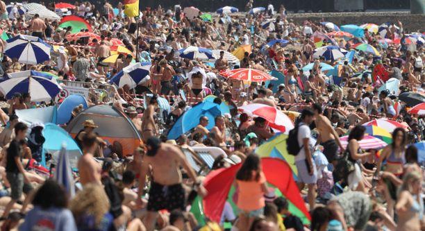 Brightonin uimarannalla sosiaalisten etäisyyksien pitäminen oli perjantaina mahdotonta.