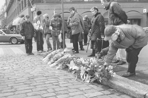 Sadat ihmiset toivat kukkia ja kynttilöitä poliisien muistoksi surmapaikalle Helsingin Tehtaankadulle vuonna 1997.