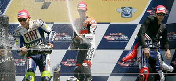 Jorge Lorenzo (oik) ei pystynyt osallistumaan Valentino Rossin ja Dani Pedrosan lailla kuohuvan suihkutteluun.