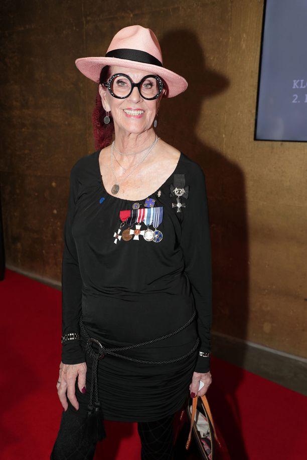 Aira Samulin edusti kunniamerkit rinnassaan elokuvan kutsuvierasensi-illassa.