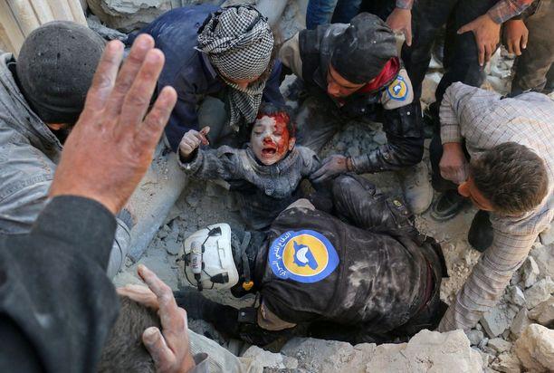 Valkoiset kypärät -järjestön vapaaehtoinen pelasti pojan raunioista Aleppossa marraskuussa 2016 tynnyripommin jälkeen. Tämä Amer Alhabin valokuva voitti palkinnon World Press Photo -kilpailussa.