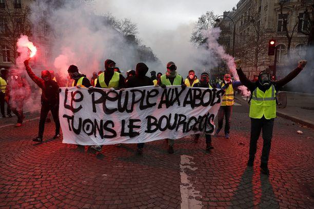 Mielenosoittajia savupommeineen lauantaina aamulla Pariisin keskustassa.