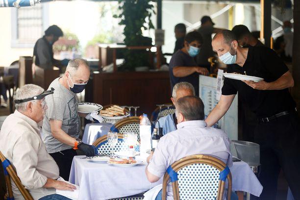 Monet maat ovat suositelleet tai velvoittaneet maskien käyttöön. Kuvassa aamiaistarjoilu Barcelonassa.