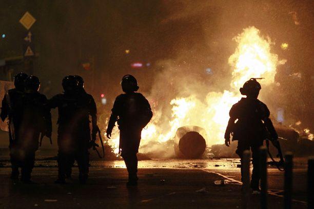 Mellakkapoliisit seisoivat liekehtivän barrikaadin edessä suurien, hallitusta vastustavien mielenosoitusten aikaan.