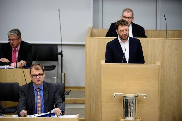 SDP:n Timo Harakka puhuu eduskunnassa lokakuussa 2015, pääministeri Juha Sipilä kuuntelee vieressä.