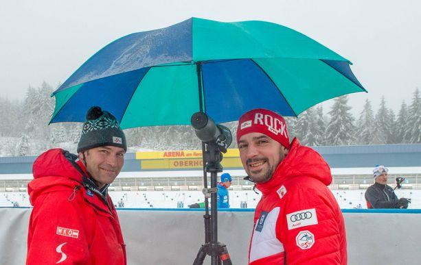Itävallan ampumahiihtomaajoukkueen valmentajat Ludwig Gredler ja Ricco Gross käyttivät sateenvarjoa Oberhofin ammuntapenkalla keskiviikkona.