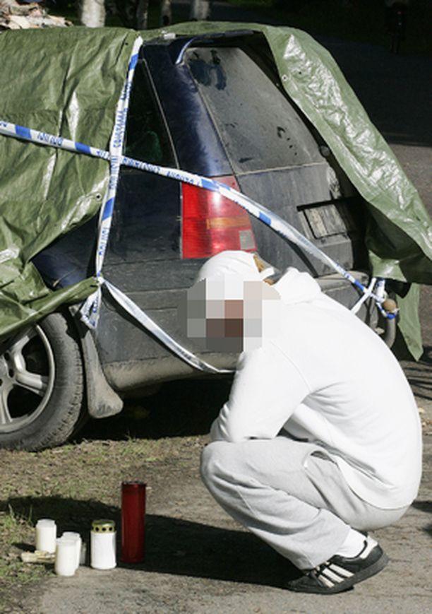 SOKKI. Kyläläiset toivat kynttilöitä romuttuneen onnettomuusauton viereen.