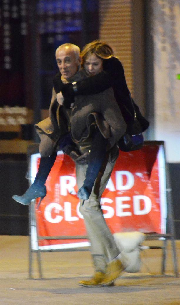 Andrew kantaa naisystäväänsä reppuselässä aamuöisessä Lontoossa.