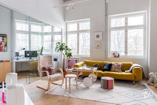 Sohva, rahi ja tyynyt tuovat vaaleaan loft-asuntoon ripauksen väriä.