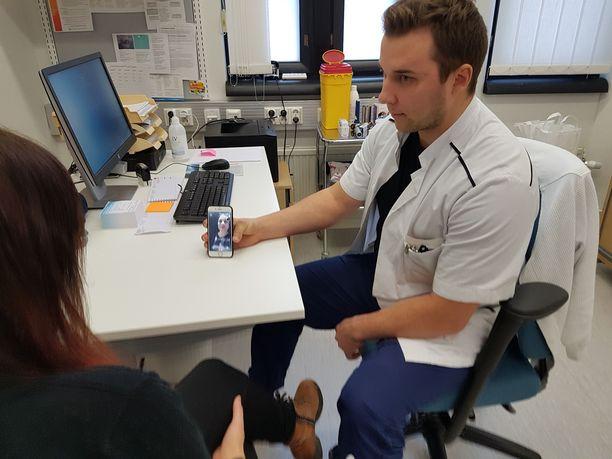 Sairaanhoitaja Juho Viiala näyttää, kuinka yhteys tulkkiin otetaan.