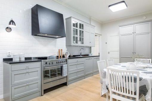 Kokopuiset kaapit ja tiililadonnalla toteutettu laatoitus tekevät tästäkin keittiöstä klassisen.