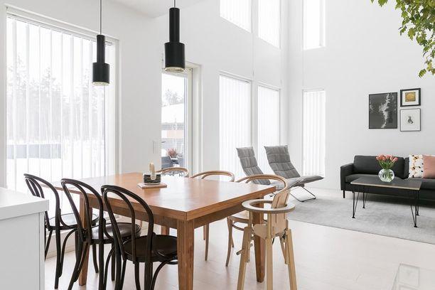 Tässä kodissa on päällekkäiset suuret ikkunat, joiden välissä on kaistale seinää. Rohkeampi skandinaavinen sisustaja yhdistelee mustia, puisia ja luonnonvärisiä huonekaluja. Näin tunnelma on lämmin.