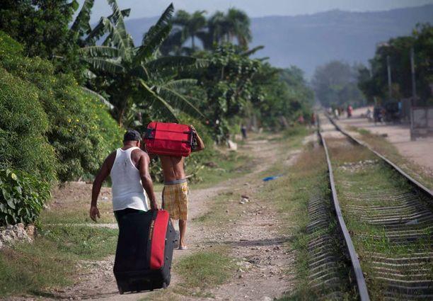 Ihmiset vetivät omaisuuttaan mukanaan muuttaessaan turvallisempaan paikkaan Paraguayn kylästä Kuubassa.