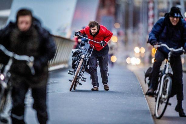 Ihmiset yrittivät pyöräillä eteenpäin voimakkaassa tuulessa Rotterdamissa.