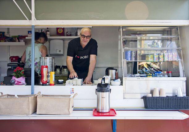 """Kari Hakala heiluu itsekin kahvilan tiskin takana. Myyntiä ei ainakaan vähennä se, että asiakkaat haluavat nähdä """"Metsolan Erkin""""."""