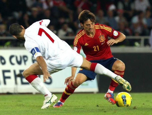 SATTUU Espanjalaispelaajilla oli kipeä ilta MM-karsinta-avauksessa. Kuvassa Espanjan David Silva yrittää ohittaa georgialaista niittokonetta Jaba Kankavaa.
