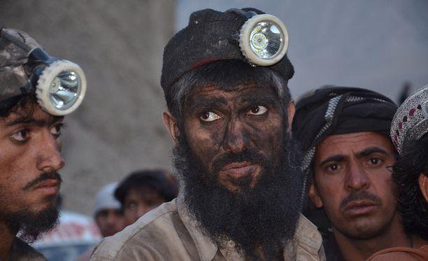 Kaivostyöläiset odottavat, että heidän toverinsa saattaisiin ulos romahtaneesta kaivostunnelista.