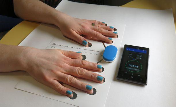 Kännykkään asetetaan yksilöity hoito-ohjelma. Kuvan sininen kontrolliyksikkö yhdistää hoitoelektrodit kännykkään langattomasti.