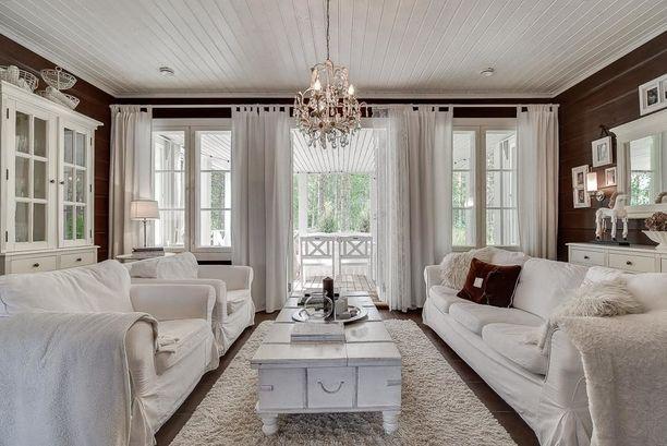 Olohuoneen parviovista aukeaa seesteinen metsänäkymä. Kodin sisustus on vastakkainen aiemmille kodeille: seinät ja lattiat ovat tummat ja myy sisustus hyvin vaalea.