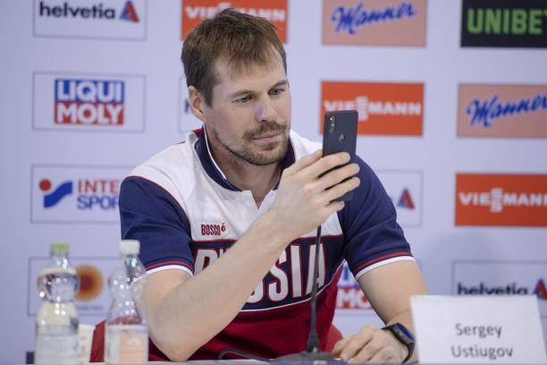 Sergei Ustjugov kuvasi puhelimellaan häntä kuvaavia mediatyöläisiä Venäjän hiihtoporukan lehdistötilaisuudessa Seefeldissä.