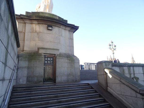 """Lontoossa Westminster-sillan kupeessa, lähellä London Eye - maailmanpyörää, sijaitsee salainen sisäänkäynti Vauxhall Crossin metroasemalle. Täällä Bond (Pierce Brosnan) tapaa pomonsa M:n (Judi Dench) elokuvassa """"Kuolema saa odottaa"""" (2002). Kyseistä asemaa ei ole oikeasti olemassa, ja todellisuudessa ovi johtaa metron huoltotunneliin. 007 Travelers vieraili täällä vuosina 2010 ja 2014."""