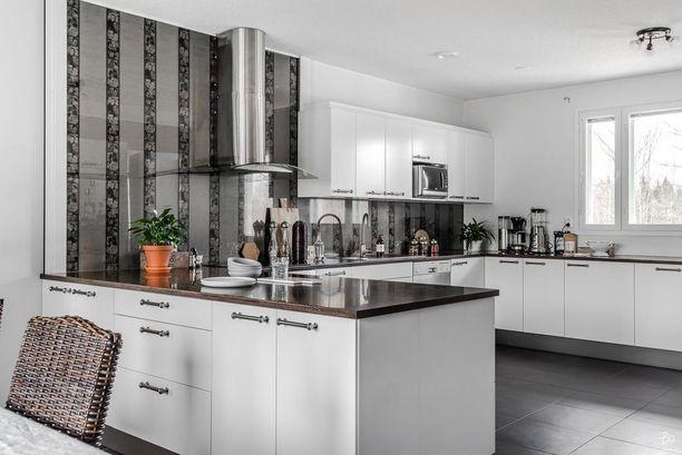 Tapetilla on helppoa tuoda ilmettä välitilaan. Keittiöön kannattaa valita kuitenkin sellainen materiaali, jota voi pyyhkiä. Tässä keittiössä tapettia suojaamaan on asennettu lasilevy.