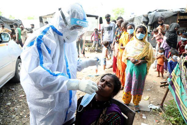Terveystyöntekijät tekevät koronatestejä slummialueella Jammussa Intiassa 16. heinäkuuta.