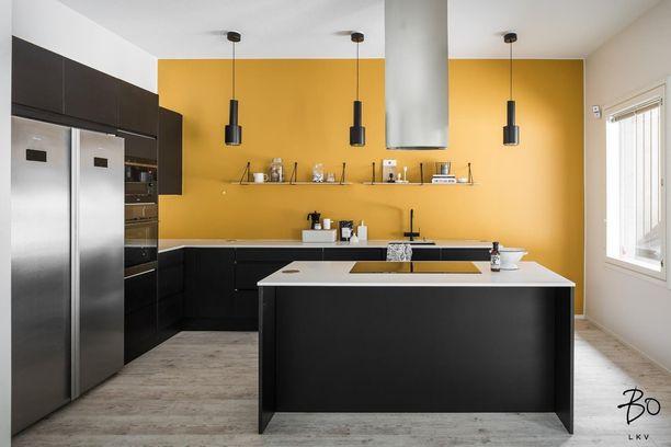 No, nyt on moderni tunnelma! Tässä keittiössä on vaikuttava keltainen seinä, hauskat loft-henkiset lamput ja raamikas muotoilu.