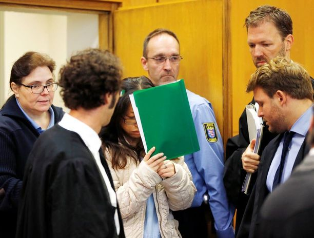 Syytetty eteläkorealaisnainen peitti kasvonsa oikeudessa Frankfurtissa tänään.