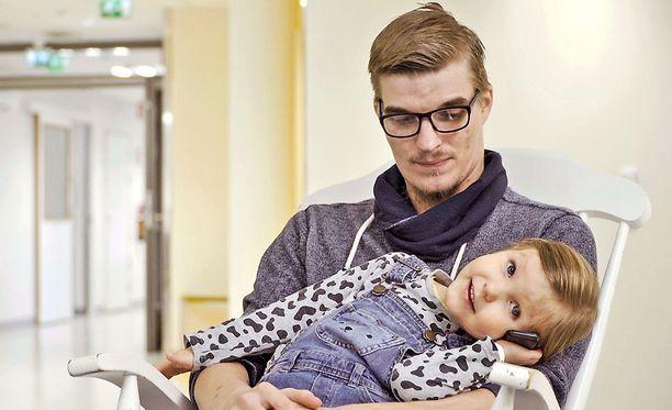 Juuso kantaa pienen tyttärensä leikkaussaliin asti.