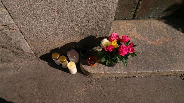 Mauno Koiviston kotirapulle on viety kukkia ja kynttilöitä.