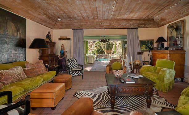 Nahka, tumma puu, vihreä ja eläinkuvio tekevät olohuoneesta tunkkaisen. Kuvassa poseeraa myös Somers itse.
